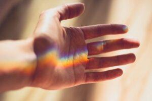 虹色の光がさしかかった手のひら