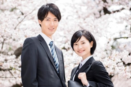 桜をバックにする男女の新入社員