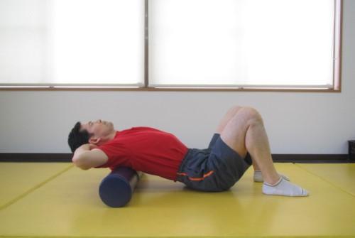 ストレッチポールを使って背骨を伸ばすエクササイズを行っている男性