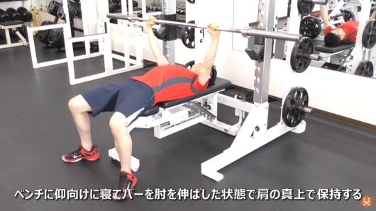 バーベルを使ってベンチプレスの開始姿勢をとっている男性