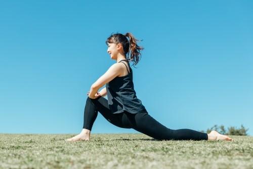 公園で腸腰筋のストレッチングをする女性