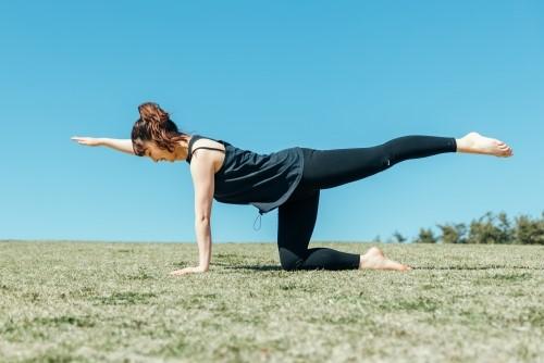 公園で四つん這いから腕を足を上げてバランスをとる女性