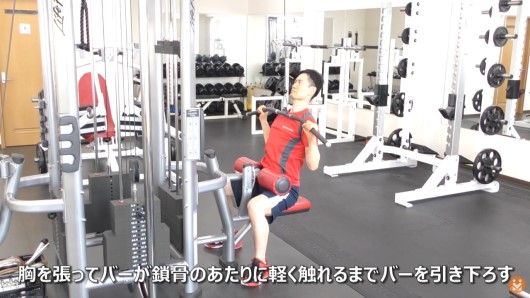 トレーニングマシンを使ってラットプルダウンのエクササイズを実施している男性