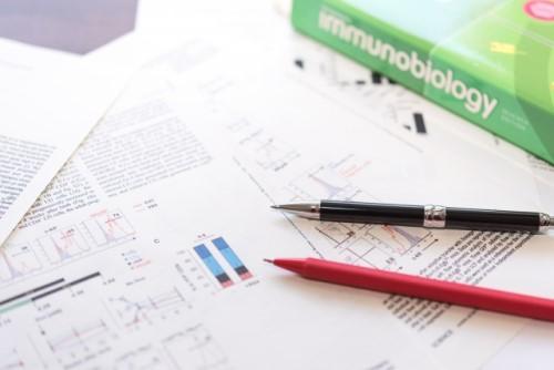 研究論文・書籍・ペンが置いてある机