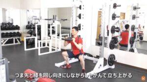 プレートを使ってワイドスタンス・スクワットのエクササイズを実施している男性