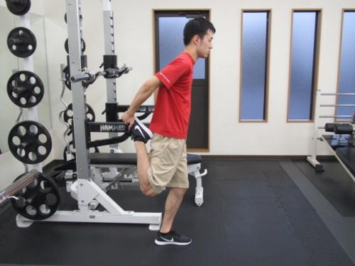ジムで大腿直筋のストレッチングをしている男性