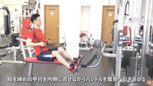トレーニングマシンを使ってシーティッドロウのエクササイズを実施している男性
