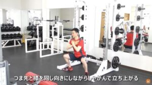 自重でワイドスタンス・スクワットのエクササイズを実施している男性
