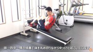 ジムで腹筋台を使ってツイスティング・シットアップのエクササイズを実施している男性